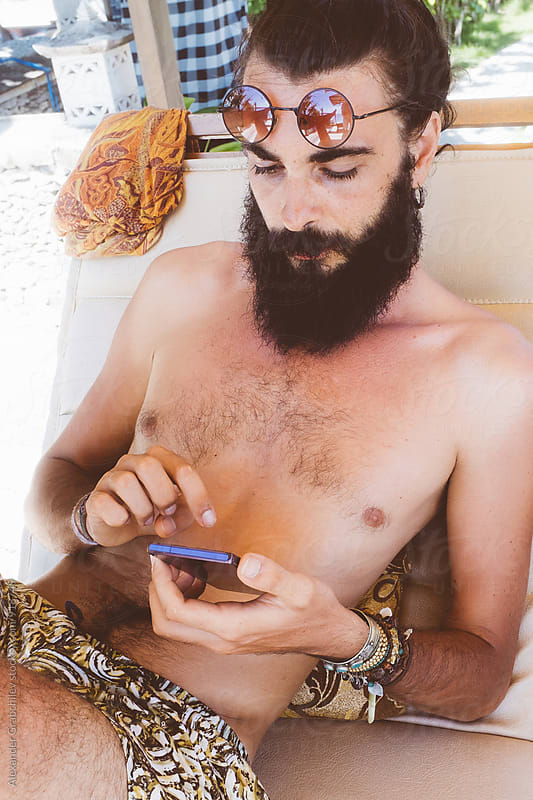 Young man using the phone on the beach by Alexander Grabchilev for Stocksy United