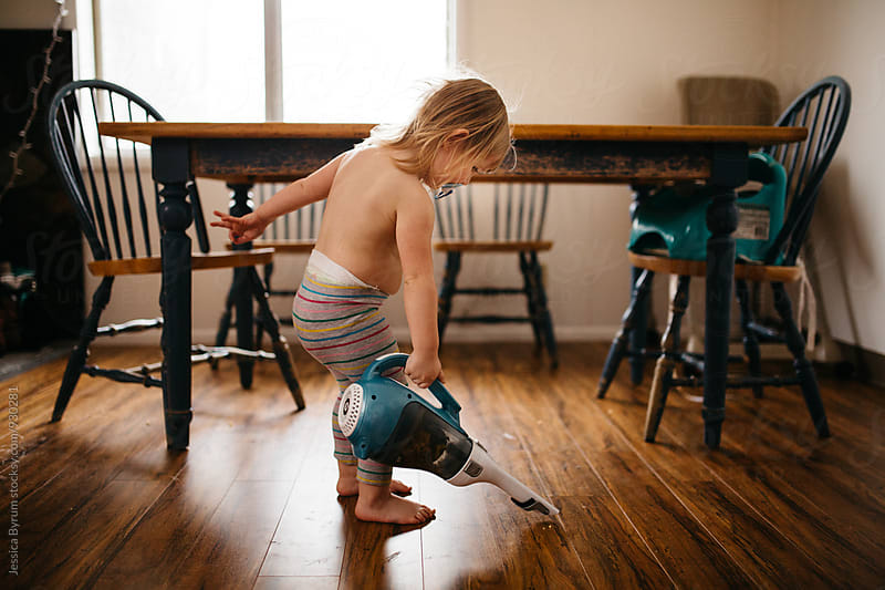 Toddler cleaning floor with handheld vacuum by Jessica Byrum for Stocksy United