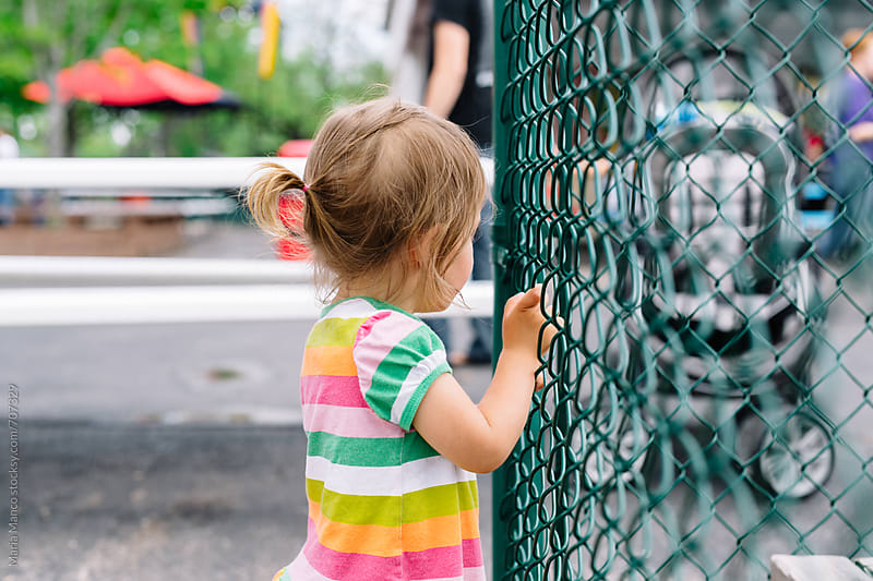 little girl leans against fence by Maria Manco for Stocksy United