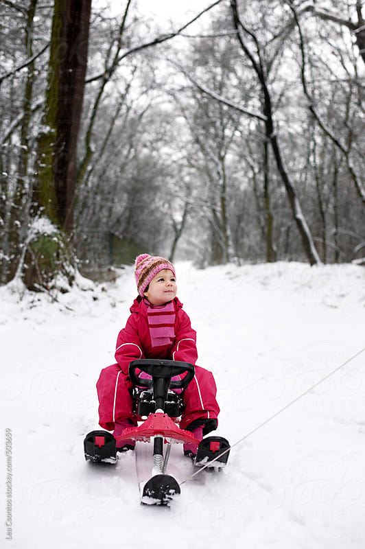 Little girl pulled and having fun on a sledge in a snow covered forest. by Lea Csontos for Stocksy United