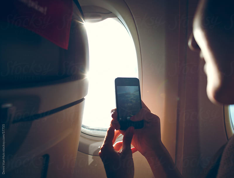 Young woman sitting in an airplane using her phone to capture the sunset outside by Denni Van Huis for Stocksy United
