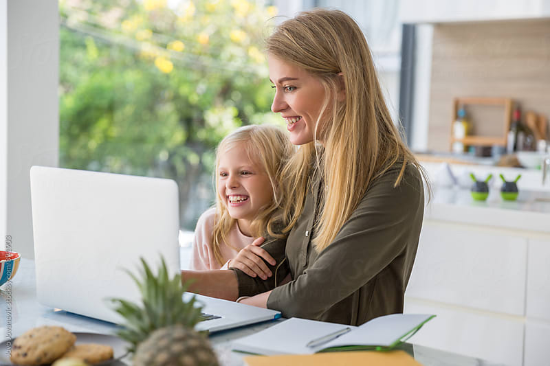 Mother and daughter looking at the laptop together by Jovo Jovanovic for Stocksy United