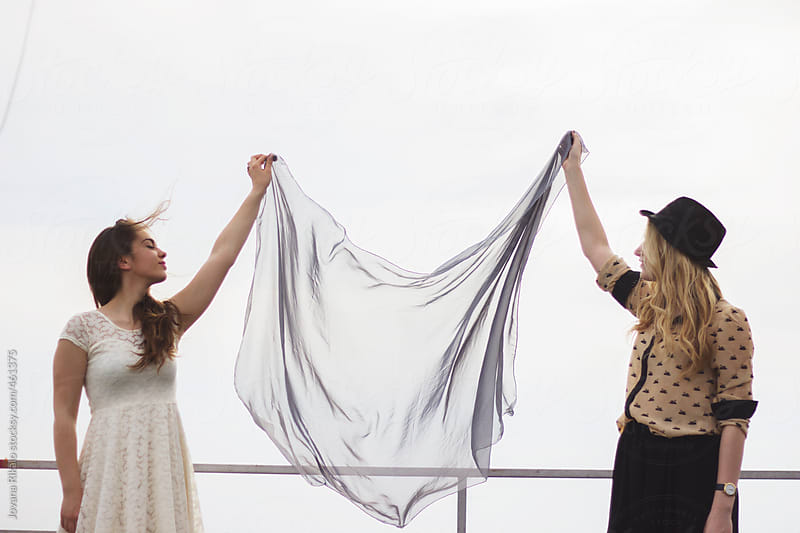 Two female friends holding a big scarf. Windy day by Jovana Rikalo for Stocksy United