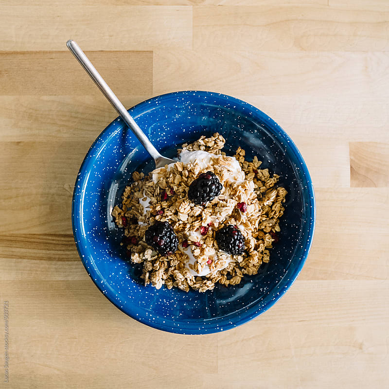 Bowl of granola, yogurt, and some black berries. by Lucas Saugen for Stocksy United