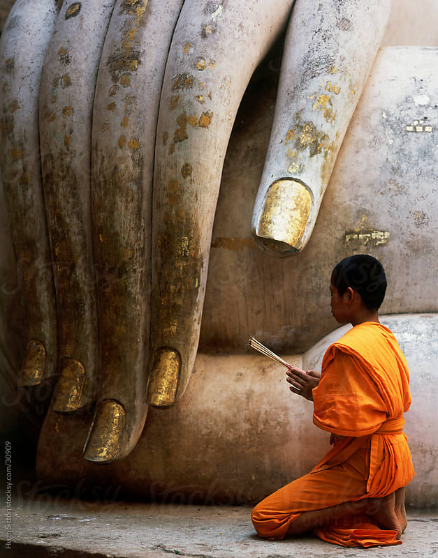 Buddhist monk praying infront of the Wat Si Chum seated Buddha. Thailand by Hugh Sitton for Stocksy United
