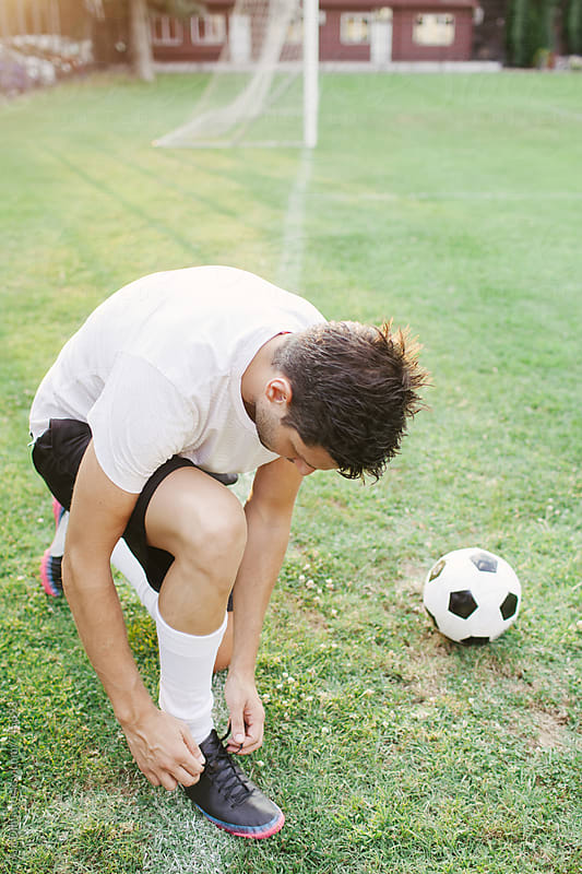 Football player tying his soccer sneakers by Ani Dimi for Stocksy United