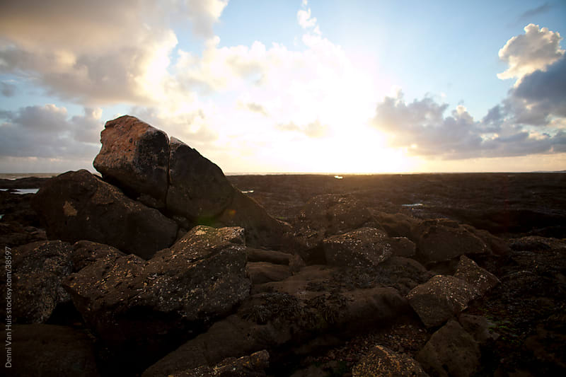 Quiet rugged lava rock shore line with a setting sun by Denni Van Huis for Stocksy United