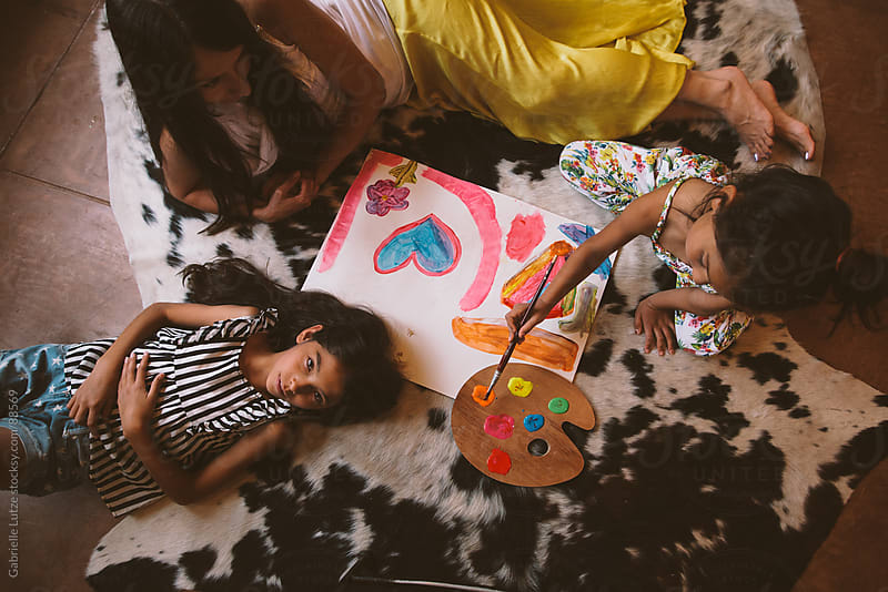 Mother and Daughters Painting Together by Gabrielle Lutze for Stocksy United