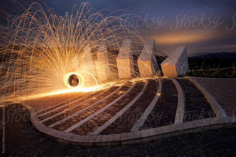 Spinning sparkle poi at communistic monument by Marko Milovanović for Stocksy United