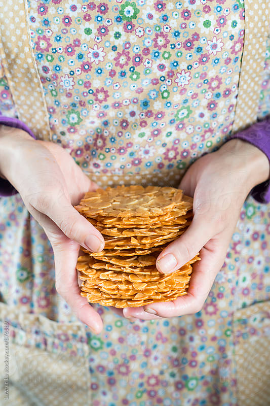 Human hands holding pile of Almond Tuiles by Lawren Lu for Stocksy United