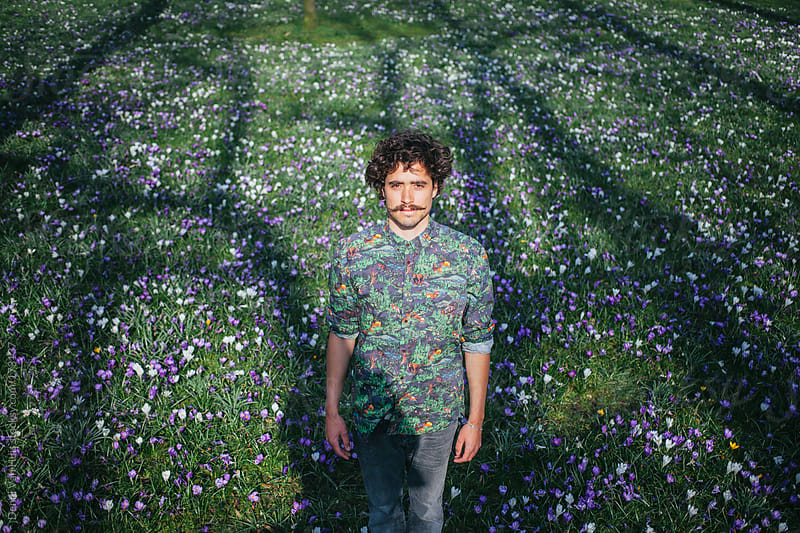 Young stylish man standing in a grass field with flowers enjoying the first days of spring by Denni Van Huis for Stocksy United