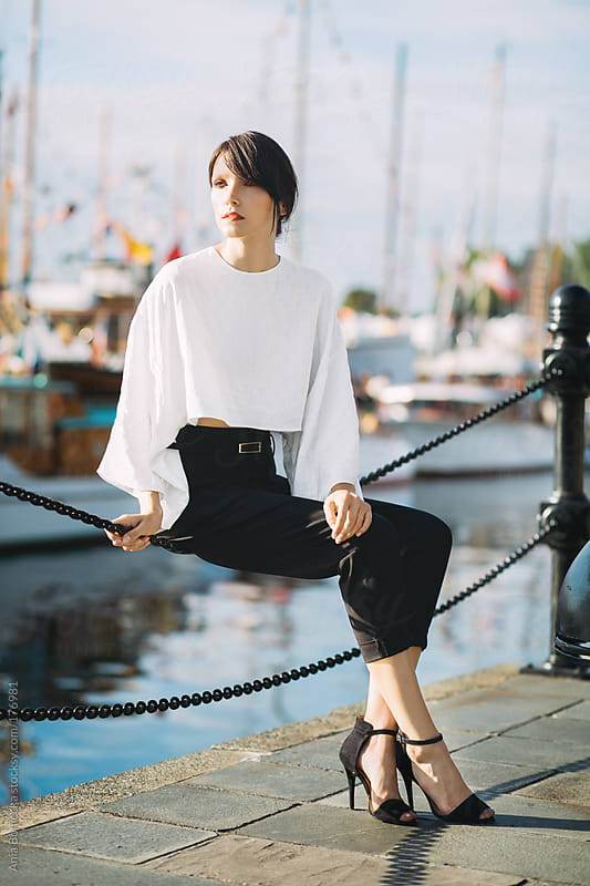 Beautiful woman sitting on a fence with boats in the background by Ania Boniecka for Stocksy United