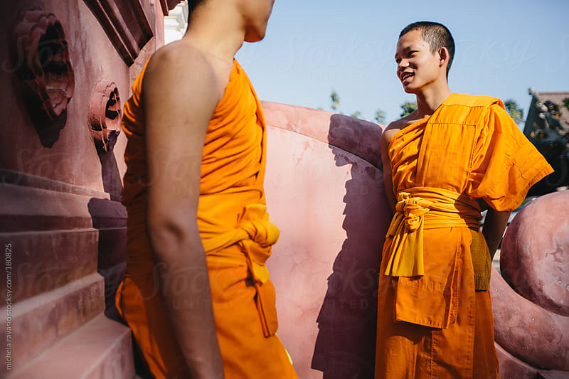 Two young Buddhist monks talking to each other outside the temple by michela ravasio for Stocksy United