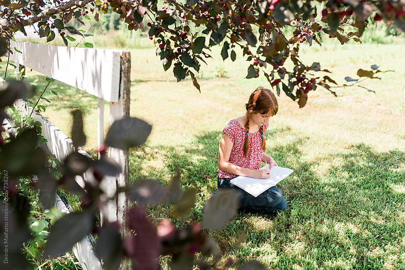 girl writing in book under tree by Deirdre Malfatto for Stocksy United