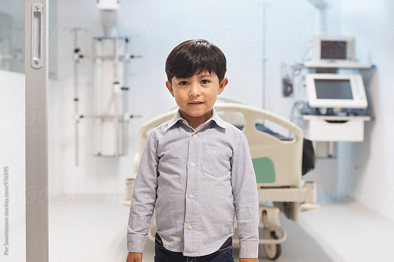 Young boy standing on the entrance to a hospital room by Per Swantesson for Stocksy United