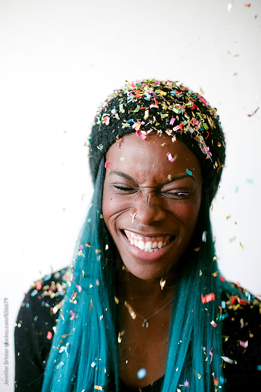 Laughing woman and confetti by Jennifer Brister for Stocksy United