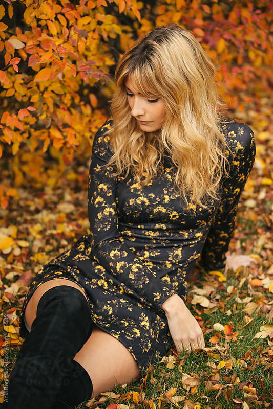 A beautiful blonde sitting down relaxing on a fall day looking down by Ania Boniecka for Stocksy United