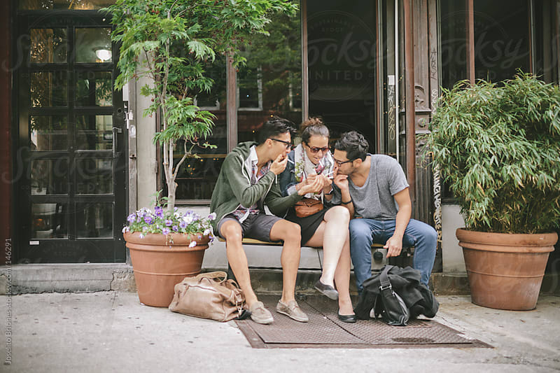 Group of Friends Hanging Out and Smoking on City Sidewalk in New York by Joselito Briones for Stocksy United