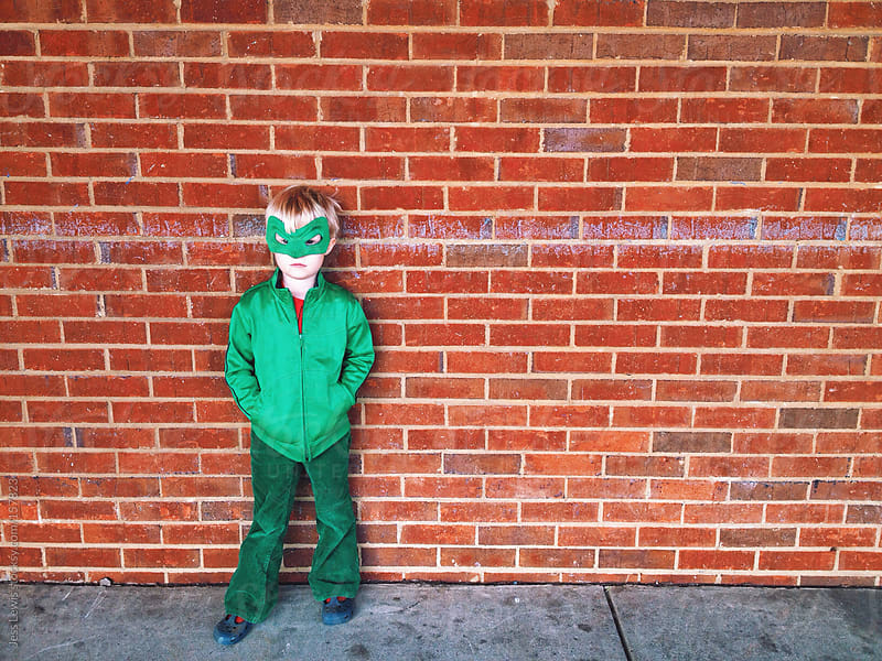 masked child standing against brick wall by Jess Lewis for Stocksy United