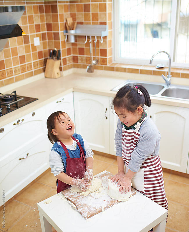 two little girls playing with flour in kitchen by Bo Bo for Stocksy United