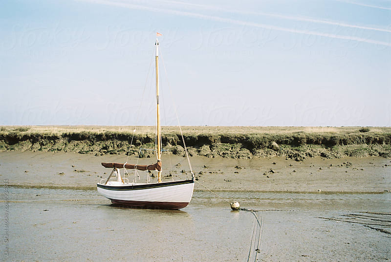 Sailing boat at low tide. Morston Quay, Norfolk, UK. by Liam Grant for Stocksy United