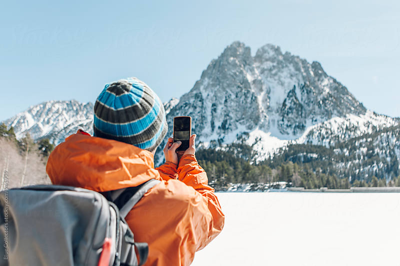 Mountaineer taking a picture of the mountain in the snowy landscape by Jordi Rulló for Stocksy United