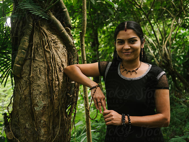 Indian girl leaning towards tree in jungle by Martin Matej for Stocksy United