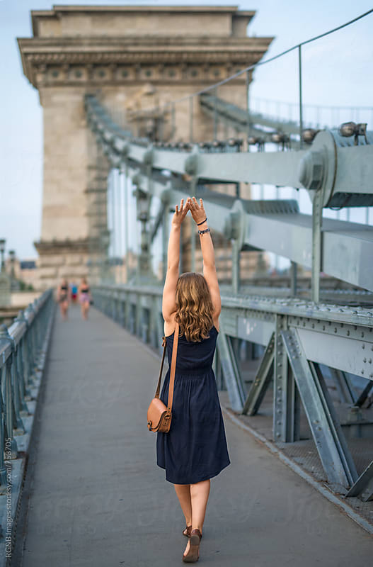 Woman walking on a bridge stretching her arms upwars by RG&B Images for Stocksy United