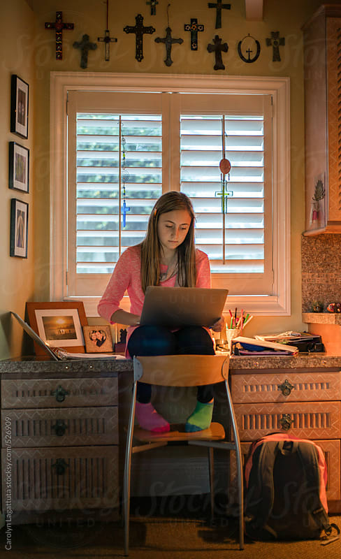 Teenage girl working on homework on her laptop by Carolyn Lagattuta for Stocksy United