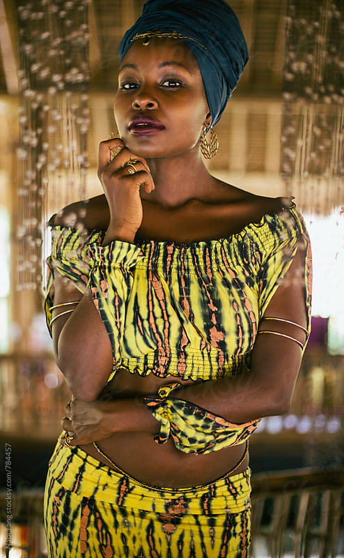 Beautiful african boho woman in tie dyed yellow clothes by Nabi Tang for Stocksy United