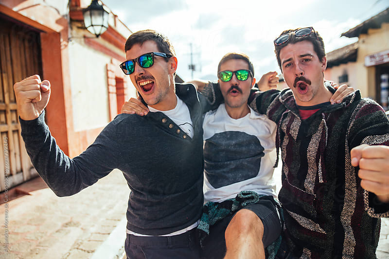 Three young happy friends together in a street of a traditional local village wearing sunglasses by Alejandro Moreno de Carlos for Stocksy United