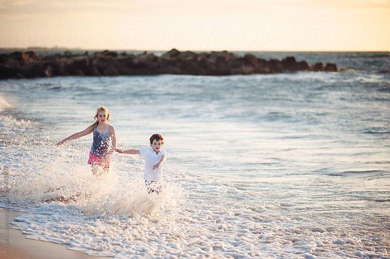 Children playing in the water at the beach by Angela Lumsden for Stocksy United