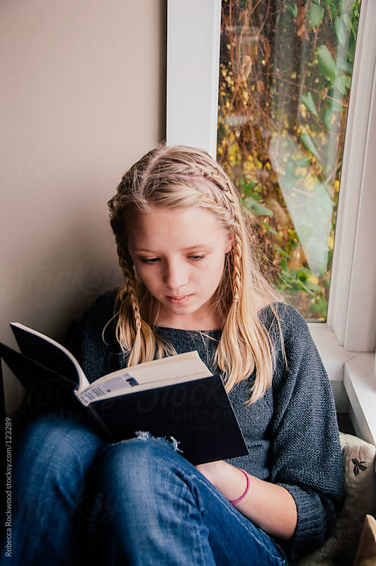 Young teenage girl reading by Rebecca Rockwood for Stocksy United