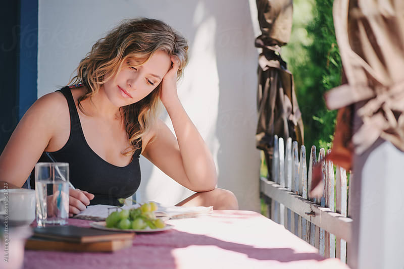 Healthy woman writing on the porch  by Aila Images for Stocksy United
