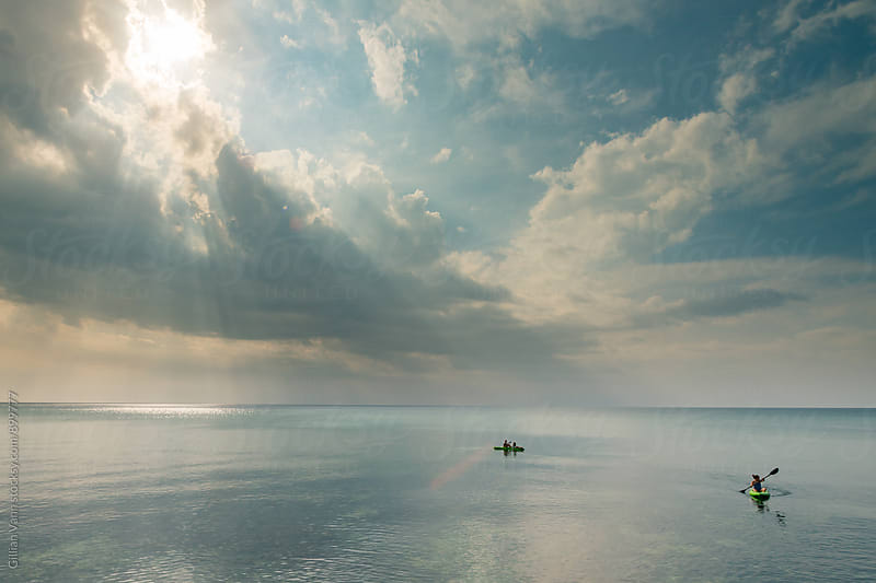 teen girls kayaking in the ocean with amazing sun rays through the clouds by Gillian Vann for Stocksy United