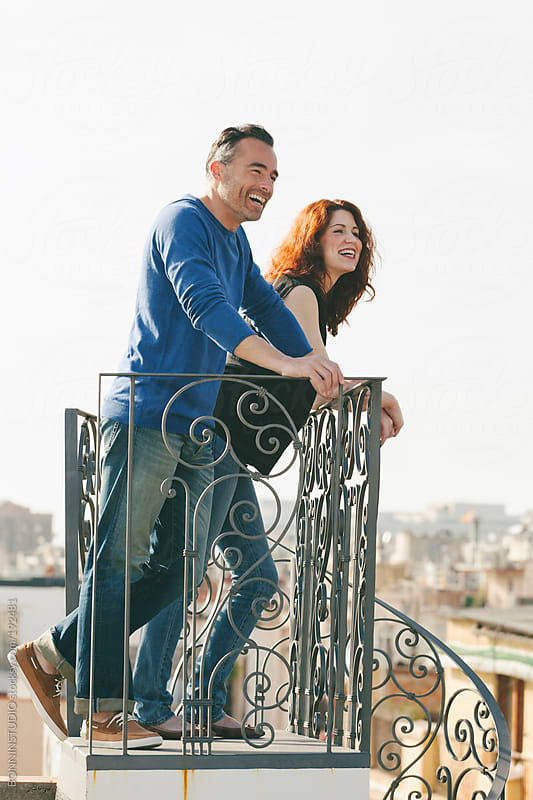 Beautiful couple smiling on the rooftop. by BONNINSTUDIO for Stocksy United
