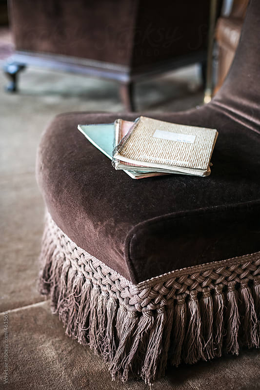Three notebooks on a armchair by Vera Lair for Stocksy United