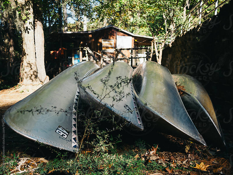 Rental canoes lined up on ground with leaves. by Jeremy Pawlowski for Stocksy United