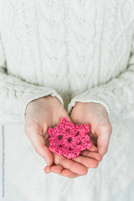 child holding a pink snowflake ornament by Jeremy and Alicia Brown Photography for Stocksy United
