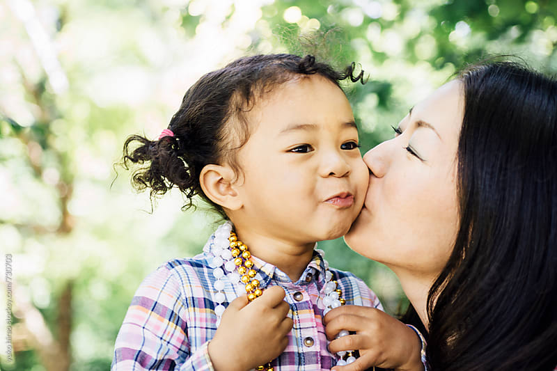 Loving diverse family-Asian mother, kissing her child by yuko hirao for Stocksy United