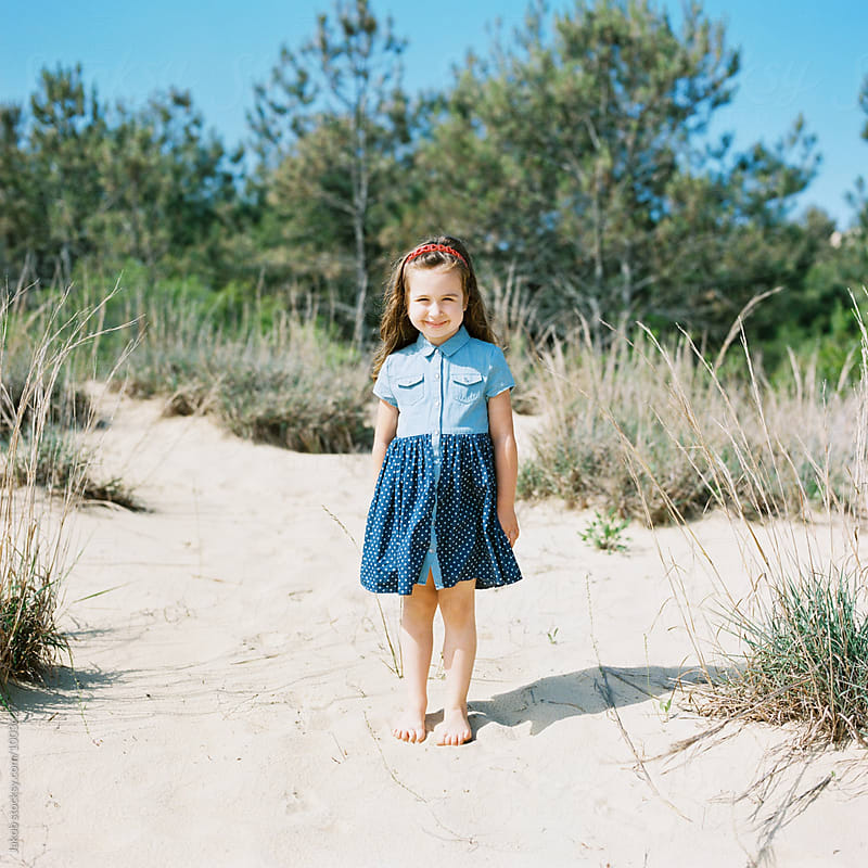 Beautiful young girl in a dress standing on a sand dune by Jakob for Stocksy United