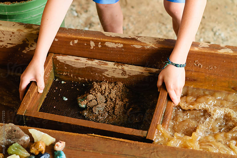 child mining for gemstones using sifting basket by Jess Lewis for Stocksy United
