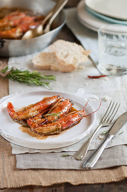 prawns cooked with honey and rosemary  by Laura Adani for Stocksy United