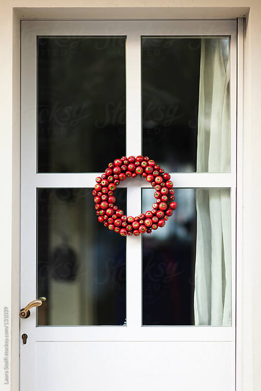 Little red apples wreath hanging on entrance door in garden by Laura Stolfi for Stocksy United