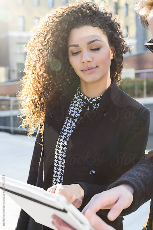 Young businesswoman looking at her notebook with a colleague by michela ravasio for Stocksy United