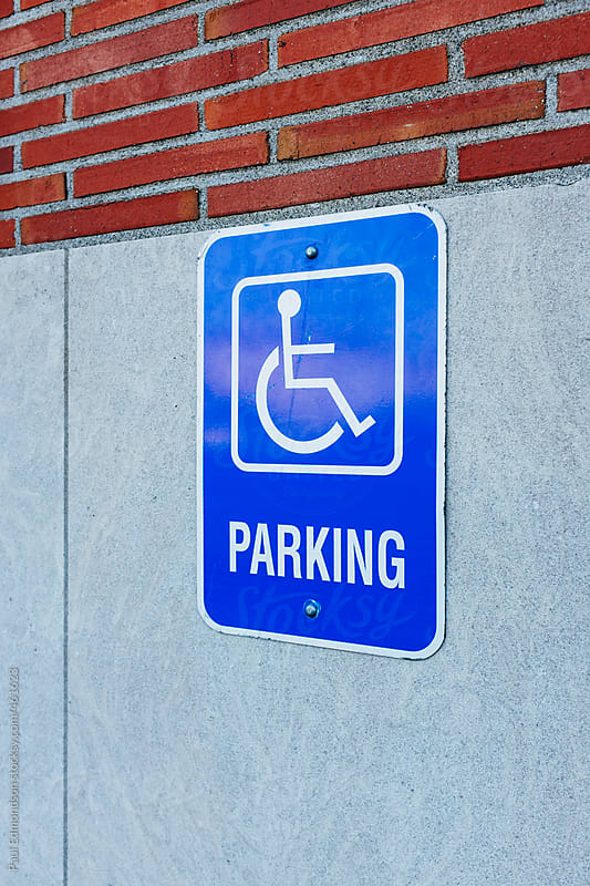 Handicapped parking sign outside building by Paul Edmondson for Stocksy United