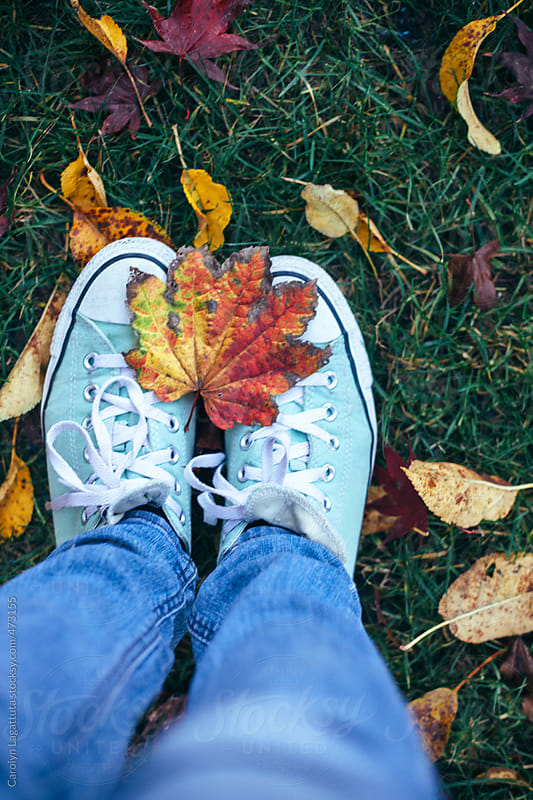 Sneakers, jeans and fall leaves by Carolyn Lagattuta for Stocksy United