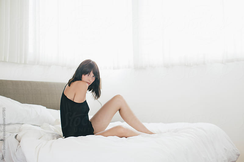 Beautiful young woman sitting on a bed by Ania Boniecka for Stocksy United