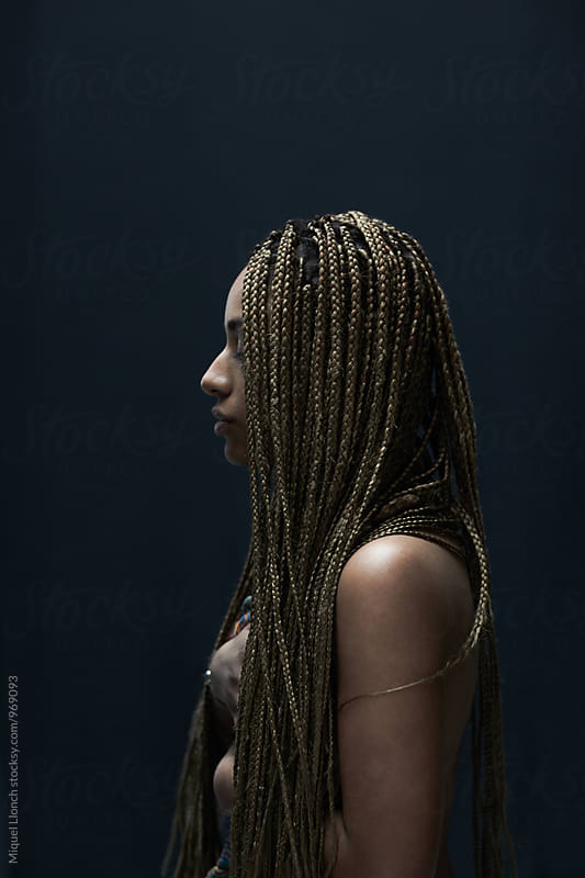 Nude portrait of a young African American woman with braided hair by Miquel Llonch for Stocksy United