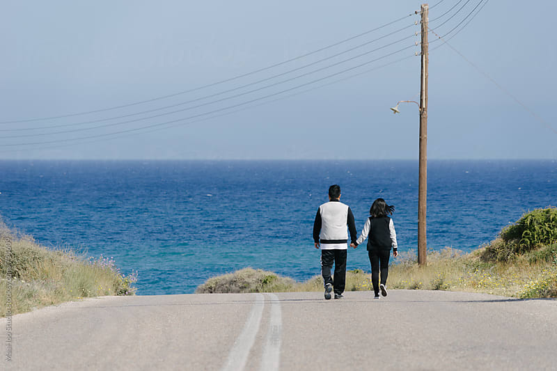 A couple walking on a sea road in Santorini by MaaHoo Studio for Stocksy United